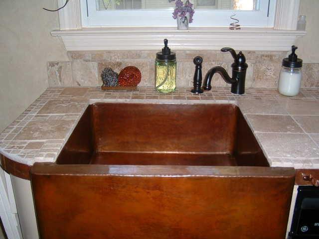 Wholesale Farmhouse Sinks : Closeup of a smooth farmhouse copper sink along a Venetian faucet on a ...
